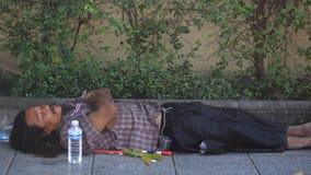 Maschio senza tetto tailandese che dorme sul sentiero per pedoni immagine stock libera da diritti