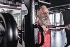 Maschio serio pensieroso con la barba che gode dell'allenamento nel centro atletico Immagine Stock Libera da Diritti