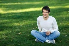 Maschio sorridente che si siede sull'erba all'aperto Immagine Stock