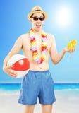 Maschio sorridente negli shorts di nuoto, tenuta una palla e cocktail Immagini Stock