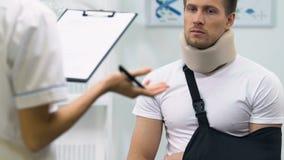 Maschio turbato in collare della schiuma ed imbracatura cervicali del braccio sull'appuntamento di medici, risultato archivi video