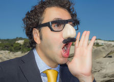 Mascked man som ropar med grouchomarx exponeringsglas Royaltyfria Foton