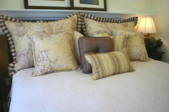 Masculine decor bed. Bed with earthtone pillows royalty free stock photography