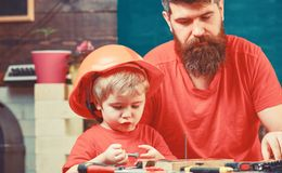 Masculine duties concept. Boy, child busy in protective helmet learning to hammering hobnails with dad. Father, parent stock photos