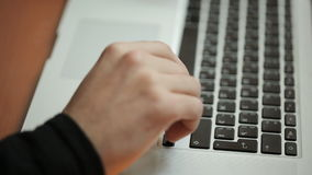 Masculine hand touches buttons on keyboard of personal computer. Manlike arm is slightly covered with hairs. Wrist is dressed in black sleeve. Laptop stands on stock footage