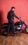 Masculine hobby concept. Hipster, brutal biker on serious face in leather jacket sits down on motorcycle. Man with beard. Biker in leather jacket near motor Royalty Free Stock Photo