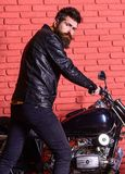 Masculine hobby concept. Man with beard, biker in leather jacket near motor bike in garage, brick wall background. Hipster, brutal biker on serious face in stock photography