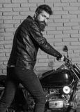 Masculine hobby concept. Man with beard, biker in leather jacket near motor bike in garage, brick wall background. Hipster, brutal biker on serious face in stock photos
