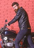 Masculine hobby concept. Man with beard, biker in leather jacket near motor bike in garage, brick wall background. Hipster, brutal biker on serious face in stock images