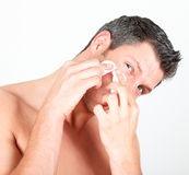 Masculine male skin care face cleaning. Man in bothroom claening face skin with batting cotton pads stock photography