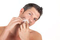Masculine male skin care face cleaning. Man in bothroom claening face skin with batting pads royalty free stock photo