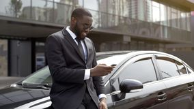Masculine man in expensive suit waiting for companion, scrolling news on gadget. Stock photo royalty free stock images