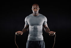 Masculine man skipping rope in dark Stock Photography