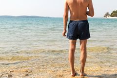 Masculine model of backs looking at the sea. Clear water, bright sun and sunscreen for sunburn. Man in blue shorts. Getting ready to go swimming in the Royalty Free Stock Photos