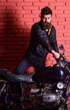 Masculine passion concept. Hipster, brutal biker on serious face in leather jacket gets on motorcycle. Man with beard. Biker in leather jacket near motor bike Royalty Free Stock Photos