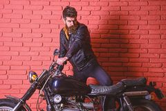 Masculine passion concept. Man with beard, biker in leather jacket near motor bike in garage, brick wall background. Hipster, brutal biker on serious face in royalty free stock photography