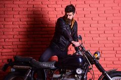 Masculine passion concept. Man with beard, biker in leather jacket near motor bike in garage, brick wall background. Hipster, brutal biker on serious face in royalty free stock images