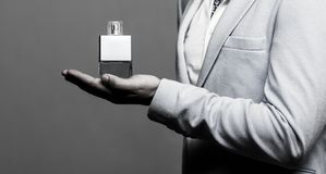 Masculine perfume, man in a suit. Man perfume, fragrance. Male holding up bottle of perfume. Perfume or cologne bottle. And perfumery, cosmetics, scent cologne royalty free stock images