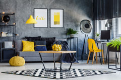 Masculine room with yellow decor. Masculine room decor with yellow lamp, chair, pouf, poster and cushions Royalty Free Stock Image