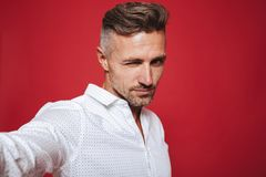 Masculine serious man 30s in white shirt taking selfie photo, is. Masculine serious man 30s in white shirt taking selfie photo isolated over red background royalty free stock images