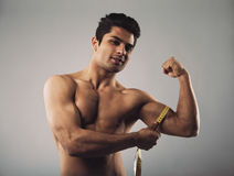 Masculine young male measuring biceps with tape measure. Fit hispanic male model measuring his body. Masculine young male measuring biceps with tape measure on Stock Photography