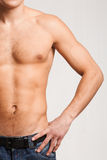 Masculinity. Torso of strong man in jeans with his arm on hip Royalty Free Stock Photography