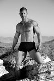 Masculinity. Muscular man in underwear standing on a rock. Taken in black and white royalty free stock photography
