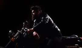 Masculinity concept. Macho, brutal biker in leather jacket riding motorcycle at night time, copy space. Man with beard. Biker in leather jacket sitting on Stock Photography