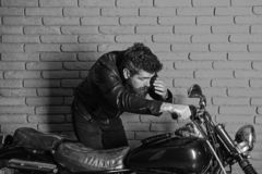 Masculinity concept. Man with beard, biker in leather jacket near motor bike in garage, brick wall background. Hipster. Brutal biker on serious face in leather royalty free stock photos