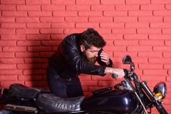 Masculinity concept. Man with beard, biker in leather jacket near motor bike in garage, brick wall background. Hipster. Brutal biker on serious face in leather royalty free stock image