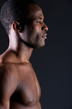 Masculinity. Side view of young African man looking away while standing against grey background Royalty Free Stock Photos