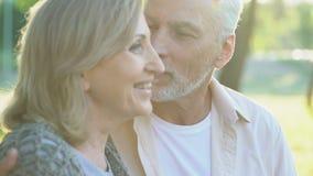 Masculino envelhecido olhando sua esposa atrativa, pensionista que beija a mulher, data romântica filme