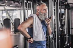 Masculino mayor confiado teniendo conversación sobre el teléfono móvil en gimnasio Imagen de archivo libre de regalías