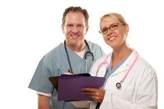 Masculino y hembra doctor a Looking Over Files Imagen de archivo