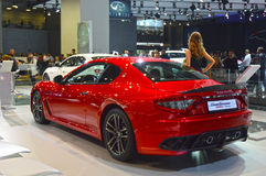 从Maserati队的一个少妇 在汽车附近的长的黑礼服 Gran Turismo 红色汽车 亮光交通 免版税库存照片