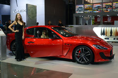 从Maserati队的一个少妇 在汽车附近的长的黑礼服 Gran Turismo 红色汽车 亮光 库存图片