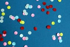 Masern Sie helle Mehrfarbenkonfettis auf blauem Hintergrund stockbilder