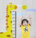 Maserte glücklicher asiatischer Stand der Nahaufnahme Kinderfür Maßhöhe mit netter Karikatur an der Marmorsteinwand Hintergrund i Lizenzfreies Stockfoto