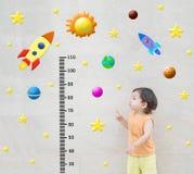 Maserten glücklicher asiatischer Stand und -punkt der Nahaufnahme Kinderzur Skala der Maßhöhe mit netter Karikatur an der Marmors Stockbilder
