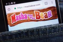 Masha et le site Web d'ours montré sur le smartphone caché dans des jeans empochent images stock