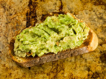 Mashed Avocado Pear On a Slice of Corn Bread. Sitting on an Oven Tray stock image