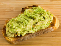 Mashed Avocado Pear On a Slice of Corn Bread. On a Wooden Chopping Board royalty free stock photography