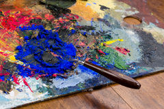 Mashed colorful oil paint with powder pigments and spatula.  Royalty Free Stock Photos
