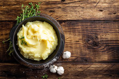 Mashed potatoes, boiled puree in cast iron pot on dark wooden rustic background, top view, copy space Stock Photography