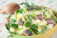 Mashed potatoes with chunks of herring and greens Stock Image