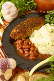 Mashed potatoes with a cutlet, beans in tomato sauce. Mashed potatoes with a cutlet and beans, surrounded by vegetables and other ingredients Stock Photography