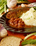 Mashed potatoes with a cutlet, beans in tomato sauce. Mashed potatoes with a cutlet and beans, surrounded by vegetables and other ingredients Stock Image