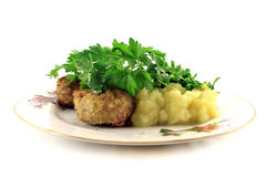 Mashed potatoes with cutlets and greens on the plate. Isolated o Stock Photography