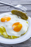 Mashed potatoes, fried eggs and pickled cucumber. Eggs from two eggs with mashed potatoes and pickles on an old table Royalty Free Stock Image