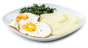 Mashed Potatoes with fried eggs and spinach isolated on white Stock Photos
